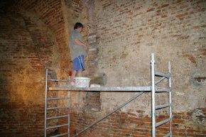 Práce v kazemate: Oprava ryhy po zvislej kanalizácii v stene bastióna.